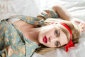 Closeup portrait of beautiful pinup blond young woman blue eyes sexy girl relaxing lying in white bed sensually looking at camera