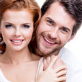 Closeup portrait of beautiful smiling couple posing at studio over white background Royalty Free Stock Photo