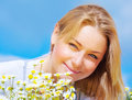 Closeup portrait of beautiful young lady resting on daisy flowers field sunny day summer vacation concept Stock Photos