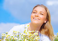 Closeup portrait of beautiful young woman with closed eyes enjoying daisy field sunny day spring nature Royalty Free Stock Photography
