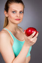 Closeup portrait of a beautiful young woman holding a red apple isolated over gray background Royalty Free Stock Photo