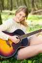 Closeup portrait of a beautiful young woman playing guitar close up happy outdoors Royalty Free Stock Photos