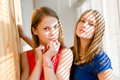 Closeup portrait of 2 best girl friends or sisters beautiful blond young women having fun posing looking at camera on sun lighted Royalty Free Stock Photo
