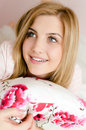 closeup portrait of blue eyes beautiful happy smiling charming young blond woman lying on bed holding pillow and looking up Royalty Free Stock Photo