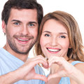 Closeup portrait of cheerful smiling couple standing together show hands heart isolated on white background Royalty Free Stock Photos
