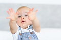 Closeup portrait of a cute baby holding out his hands over blurred background Royalty Free Stock Photography
