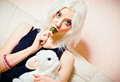 Closeup portrait of cute blonde girl with candy and rabbit toy a Royalty Free Stock Image