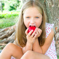 Closeup portrait of a cute little girl eating apple at park Royalty Free Stock Photos
