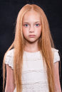Closeup portrait of cute little girl with redhead hair in studio over dark background. Royalty Free Stock Photo