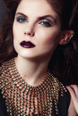 Closeup portrait with deep blue eye, creative makeup and golden accessories Royalty Free Stock Photo