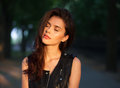 Closeup portrait of dreamy young beautiful brunette woman in black leather jacket posing with closed eyes on sunset outdoors  with Royalty Free Stock Photo