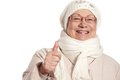Closeup portrait of elderly woman with thumb up at wintertime smiling Royalty Free Stock Photo