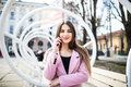 Closeup portrait of enjoyed brunette girl speaking on phone on street. She wears pink jacket, smiling to camera Royalty Free Stock Photo