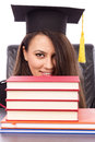 Closeup portrait of a happy female student with graduation cap peeking behind books on white background Stock Photography