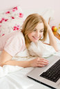 Closeup portrait of happy smiling beautiful gentle sweet young business woman blue eyes girl in bed working on laptop computer Stock Image