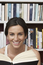 Closeup portrait of happy woman with book against shelves young at home Royalty Free Stock Images