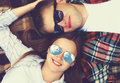 Closeup portrait of happy young couple in sunglasses lying on the plaid together top view Royalty Free Stock Image