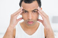 Closeup portrait of a man suffering from headache young in bed at home Royalty Free Stock Images