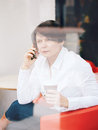 Closeup portrait of middle age Caucasian white business woman sitting in cafe restaurant with cup of coffee talking over on phone Royalty Free Stock Photo