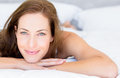 Closeup portrait of a pretty woman lying in bed smiling young at home Royalty Free Stock Photography
