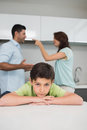 Closeup portrait of sad son while parents quarreling a in the kitchen Royalty Free Stock Photo
