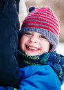 Closeup portrait of smiling laughing Caucasian white toddler boy child in winter clothes hugging his mother parent outside Royalty Free Stock Photo