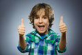 Closeup portrait successful happy boy show thumb up isolated grey background.
