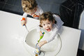 Closeup portrait of twins kids toddler boy girl in bathroom toilet washing face hands brushing teeth with toothbrash Royalty Free Stock Photo