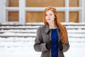 Closeup portrait of young beautiful redhead lady in blue dress and grey coat at winter outdoors Royalty Free Stock Photo