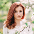 Closeup portrait of young beautiful redhead woman with an apple tree branch