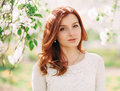 Closeup portrait of young beautiful redhead woman with an apple tree branch Royalty Free Stock Photo