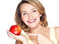 Closeup portrait of a young beautiful smiling woman pointing the finger at apple isolated on white Royalty Free Stock Photos