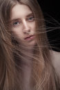 Closeup portrait of young blond woman with long flying hair on dark background Stock Photos