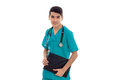 Closeup portrait of young handsome brunette man doctor in blue uniform with stethoscope and board in hands looking at Royalty Free Stock Photo