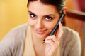 Closeup portrait of a young happy woman talking on a phone at home Royalty Free Stock Photos