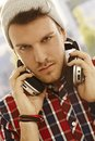 Closeup portrait of young man with headphones using wearing cap outdoors Royalty Free Stock Photography