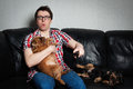 Closeup portrait, young man in the red shirt, sitting on black leather couch with two dogs, watching TV, holding remote, surprised Royalty Free Stock Photo