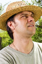 Closeup portrait of a young man with straw hat looking up in an orchard Royalty Free Stock Images