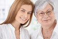 Closeup portrait of young woman and mother smiling attractive women senior both looking at camera Stock Photo