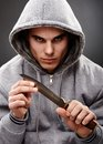 Closeup pose of a dangerous gangster portrait threatening mafia man holding knife in his hands over gray background representing Stock Photography