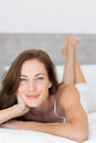 Closeup of a pretty smiling woman lying in bed portrait young at home Stock Photography