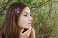 Closeup profile of young female with flower in her hair and fingers touching her face Royalty Free Stock Photos