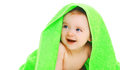 Closeup protrait of cute smiling baby under the bright green towel on a white background Stock Image
