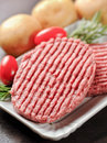 Closeup raw hamburgers on wooden table Royalty Free Stock Photo