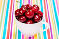 Closeup of red cherries with water drops in white cup on varicolored background Royalty Free Stock Photo