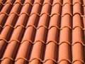 Closeup of the red clay roof tiles. Shingles. Old and used overlapping red classic style roofing material texture Royalty Free Stock Photo
