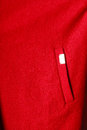 Closeup red coat with pocket as background texture fragment of casual and metal sign Royalty Free Stock Photography