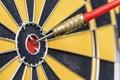 Closeup red dart arrow hitting in target bullseye of dartboard Royalty Free Stock Photo