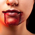 Closeup of red lips of a young girl with blood flowing by Royalty Free Stock Photo