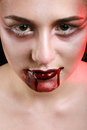 Closeup of red lips of a young girl with blood flowing by Stock Photo